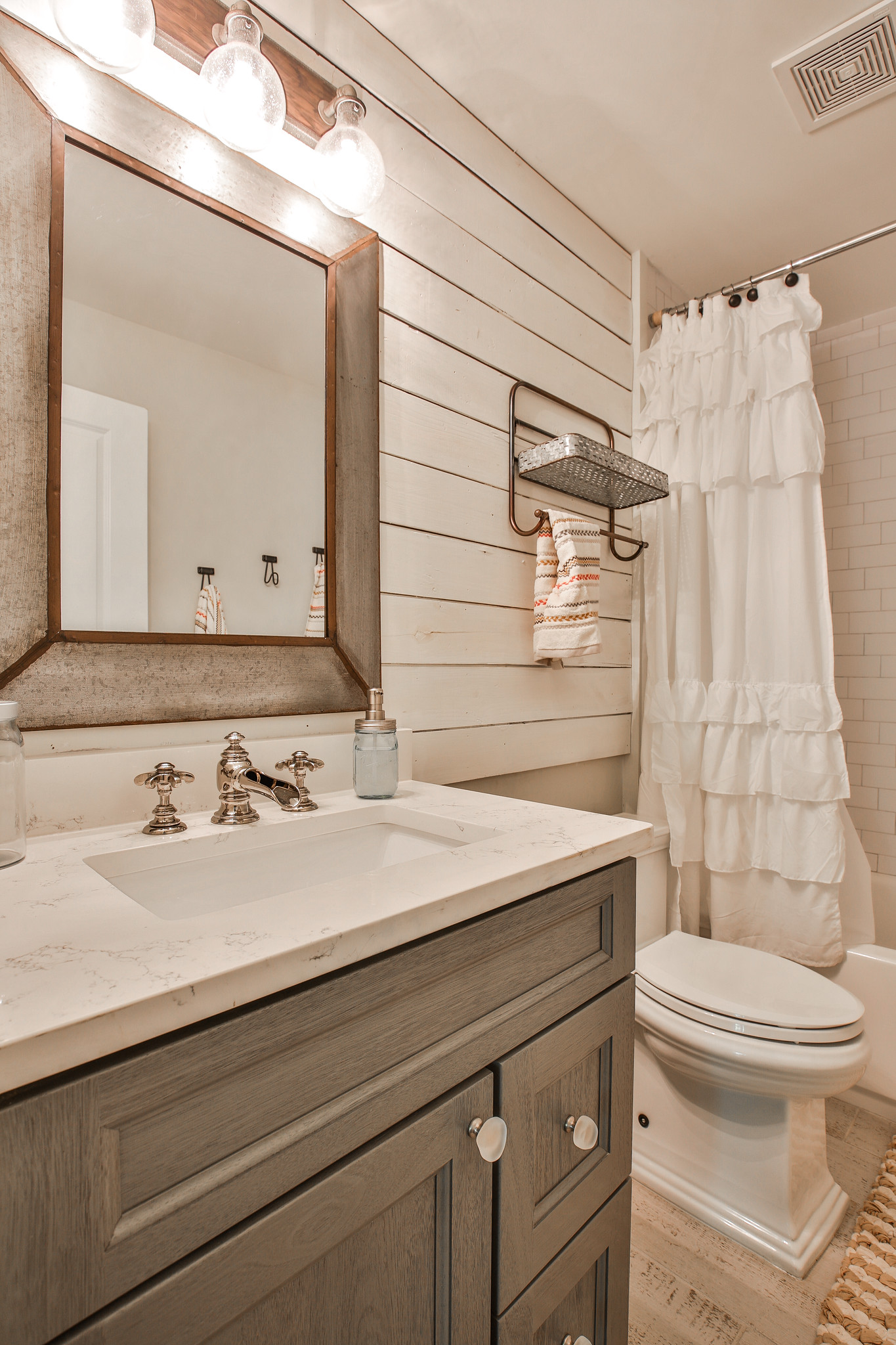 Custom vanity: Forevermark Cabinetry, Drawer knobs: Liberty Hardware, Counter: Hanstone Quartz . Plumbing fixtures, faucets, sink, toilet: Kohler, Lighting: Savoy House.